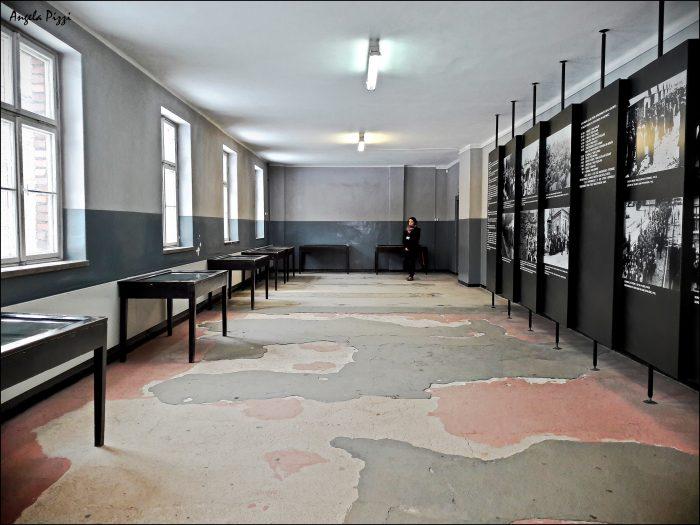 Raggiungere Auschwitz partendo da Cracovia. All'interno di uno dei blocchi. Una stanza semivuota con delle teche contenenti documenti e sulla destra dell'immagine alcune bacheche sulle quali sono esposte foto e didascalie, nonchè alcuni dati storici