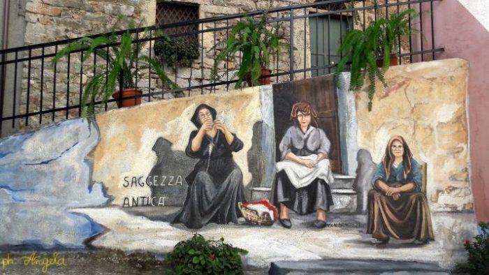 La bellezza dell'ospitalità sarda e saggezza antica. Uno dei murales presenti a Orgosolo (Nu)
